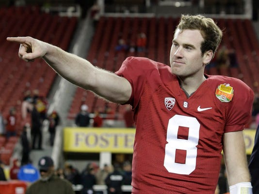 FILE - In this Tuesday, Dec. 30, 2014, file photo, Stanford quarterback Kevin Hogan points to his teammates as he is named offensive MVP after a 45-21 win over Maryland during the Foster Farms Bowl NCAA college football game in Santa Clara, Calif. Hogan will return to school as a fifth-year senior, opting to make one more run with the Cardinal next season instead of enter the NFL draft or pursue other career paths.  Hogan announced his decision via Twitter on Thursday, Jan. 15, 2015, the final day for underclassman to declare for the draft. (AP Photo/Marcio Jose Sanchez, File)