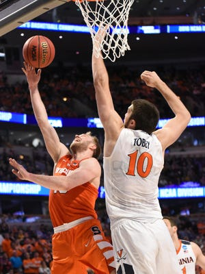 Syracuse guard Trevor Cooney (10) shoots against Virginia center Mike Tobey (10) during the championship game of the midwest regional of the NCAA Tournament .