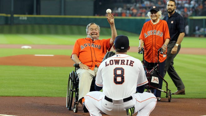 Oct 11, 2015; Houston, TX, USA; Former president George H. W. Bush throws out the ceremonial first pitch to Houston Astros third baseman Jed Lowrie (8) as Barbara Bush (right) looks on prior to game three of the ALDS against the Kansas City Royalsat Minute Maid Park. Mandatory Credit: Troy Taormina-USA TODAY Sports