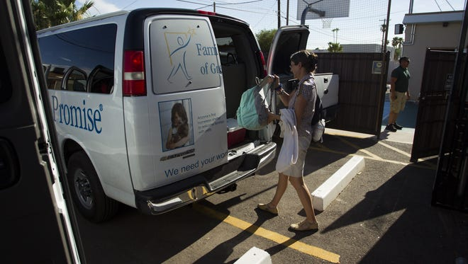 A woman loads her belongings into a van at Family Promise of Greater Phoenix in Scottsdale. The family-oriented homeless shelter houses families in a network of interfaith congregations.
