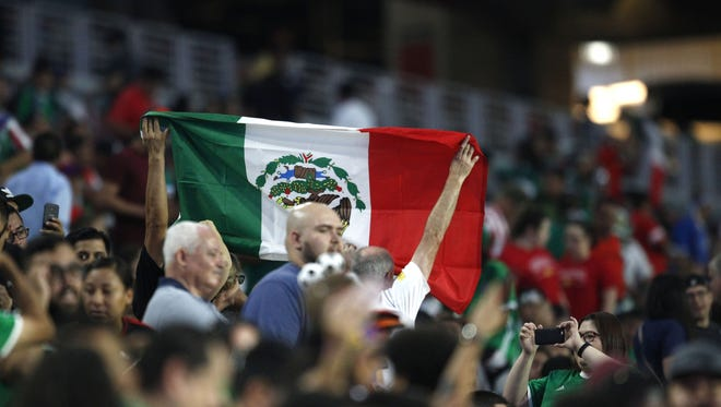 Mexico fans hold up a Mexican flag during the second half of a CONCACAF Gold Cup quarterfinal soccer match against Jamaica in Glendale, Ariz. on Thursday July 20, 2017.