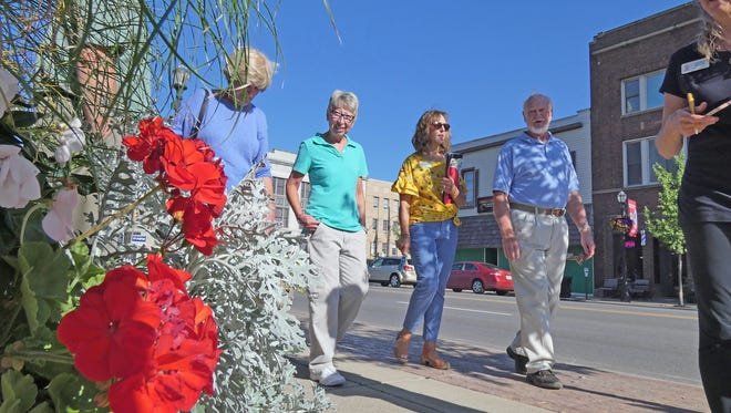 Pam Siegenthaler, Kim Hildreth, Teresa Woodard and Jim Kulig tour the Park Avenue West area on Thursday to view the downtown Mansfield area during the America in Bloom judging.