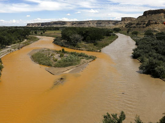 The confluence of the Animas and San Juan Rivers is pictured Aug. 8, 2015, after the Gold King Mine spill. A plume of toxic mine waste is seen in the Animas River, at left, as it merges with the San Juan River, at right.