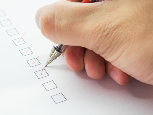 man is checking on list with red pen