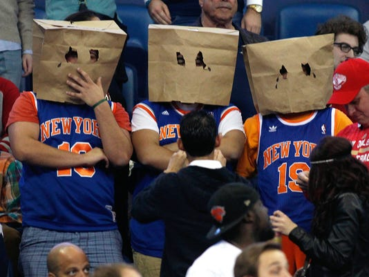 """New York Knicks' fans stand during the second half of an NBA basketball game against the New Orleans Pelicans in New Orleans, Tuesday, Dec. 9, 2014. No team has more losses than the Knicks. Only Detroit has as many. Some fans in Knicks jerseys wore brown paper grocery bags over their heads, as fans of the """"Aints"""" once did in the Superdome next door when the Saints were at their worst. (AP Photo/Jonathan Bachman)"""