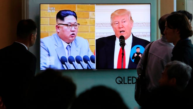 People watch a TV screen showing file footage of President Trump and North Korean leader Kim Jong Un during a news program at the Seoul Railway Station in Seoul, South Korea.