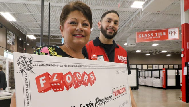"""Manager David Roman presents Roberta Prospeck of Brookfield with a million dollar prize paid through a $25,000 annual annuity that she won by rolling six dice to spell """"Floors"""" at the Floor & Décor store in a """"FLOORS Dice Roll Challenge"""" where she ended up beating the 1 in 46,656 odds."""