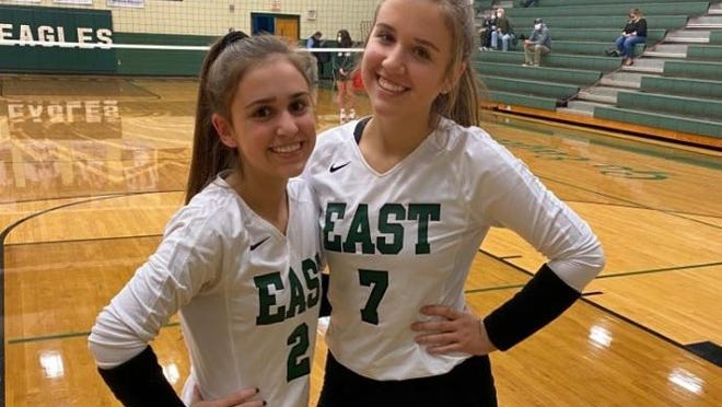 East Henderson volleyball sisters Emma, left, and Molly pose before Monday night's match at home against Polk County.