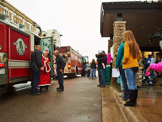Mrs. Claus exiting the fire truck after arriving at Lakeview Square Mall on Saturday.