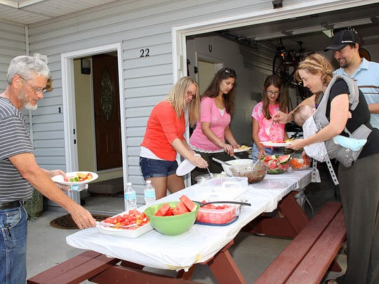 Tony Boatman, Brittany Sullivan, Julie and Sienna Ellingson, and Chad and Mistina Leitheiser, residents of Rose Court in Windsor, line up for a feast during Tuesday's National Night Out festivities.