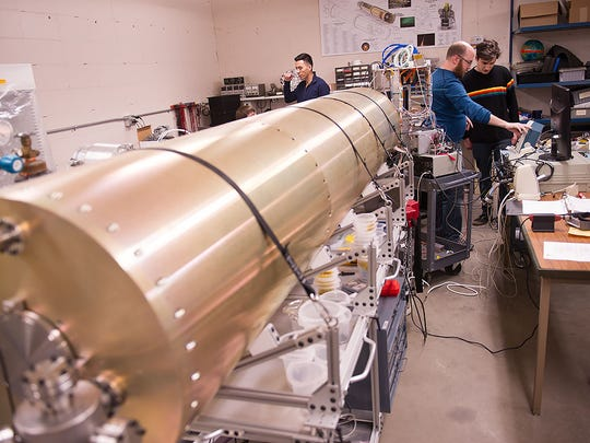 The rocket payload sits in the lab while a University of Iowa team of physics and astronomy researchers check the electronics.