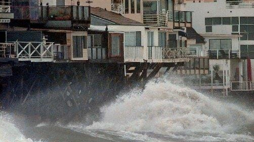 """Wind-driven waves from a powerful Pacific storm crash against oceanfront homes along the Pacific Coast Highway in Malibu, Calif., during an El Nino storm in the winter of 1997-98. Scientists are on the watch for how El Nino, combined with warm """"blobs"""" of water in the Pacific might impact the coming winter."""