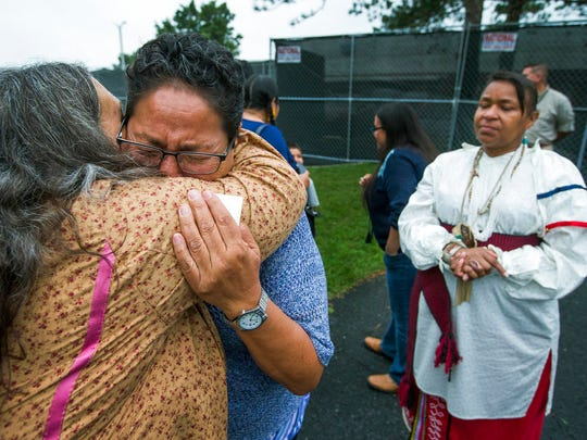 In this Monday, Aug. 7, 2017 file photo, Millie Friday, a descendent of Little Plume, a Native American student who was taken from his family and forced to go to boarding school, is comforted by Barbara Andrews-Christy of Circle Legacy Center, as Aílice Hall looks during a gathering on the grounds of the Carlisle Barracks, in Carlisle, Pa. The forced separation of Latino migrant children from their parents has generated strong condemnation of President Trump's immigration policies but it's not the first time the U.S. government or authorities have been involved in separating children from their families.