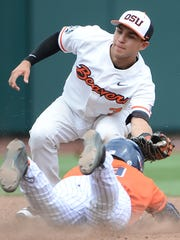 Oregon State Beavers infielder Nick Madrigal (3) tags Cal State Fullerton Titans infielder Dillon Persinger (19) in the third inning at TD Ameritrade Park Omaha