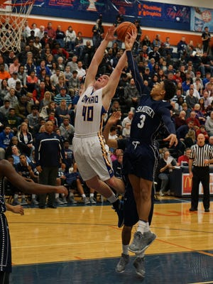Ontario's Andrew Rathburn jumps for a rebound against Sandusky during a tournament game in a packed house in Galion earlier this season. The Warriors will join the Mid Ohio Athletic Conference after next season.
