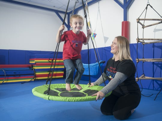 Julie LaRochelle, who owns We Rock the Spectrum - Mount Laurel with her husband, Charlie, watches as her son Shane, 4, plays in the gym. The space features swings, climbing structures, arts and crafts, and a calming room.