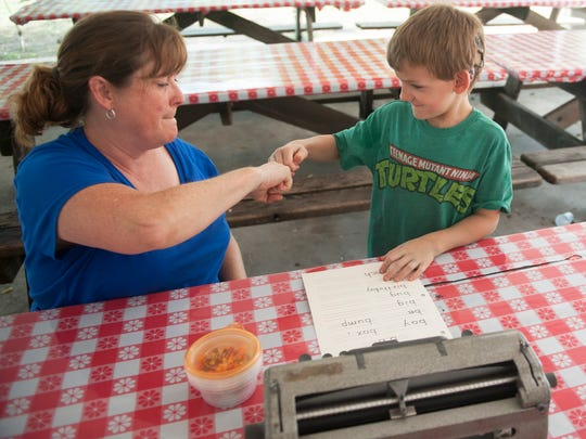 Henry Norton, 6 of Mount Laurel,  who was born deaf and is now nearly blind from a rare genetic disease called Usher syndrome gets fist bumped by deafblind intervener Lauri Wendel after Norton successfully completed an exercise of spelling words with a braille writer at Liberty Lake Day Camp in Bordentown.  08.13.14
