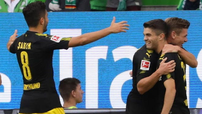 Dortmund players celebrate the opening goal by Christian Pulisic.