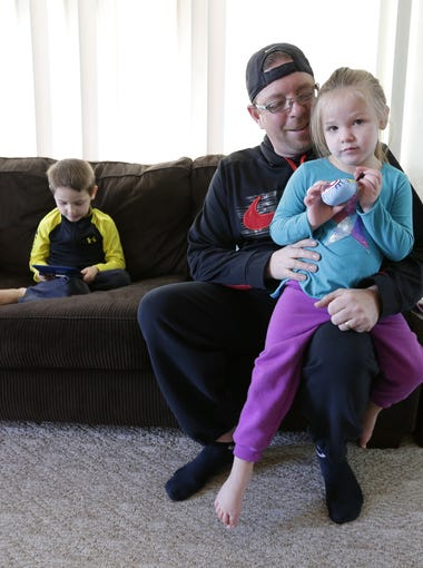 Rob Brooks holds Charlie, 3, on the couch at their