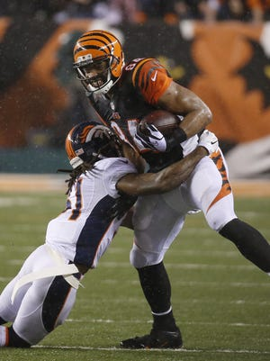 Jermaine Gresham (84) is tackled by Broncos strong safety Omar Bolden in the fourth quarter of last season's Dec. 23 game at Paul Brown Stadium.