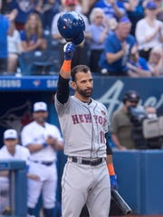 New York Mets' Jose Bautista acknowledges the crowd in his first at-bat in the team's baseball game against the Toronto Blue Jays, his former team, Tuesday, July 3, 2018, in Toronto.