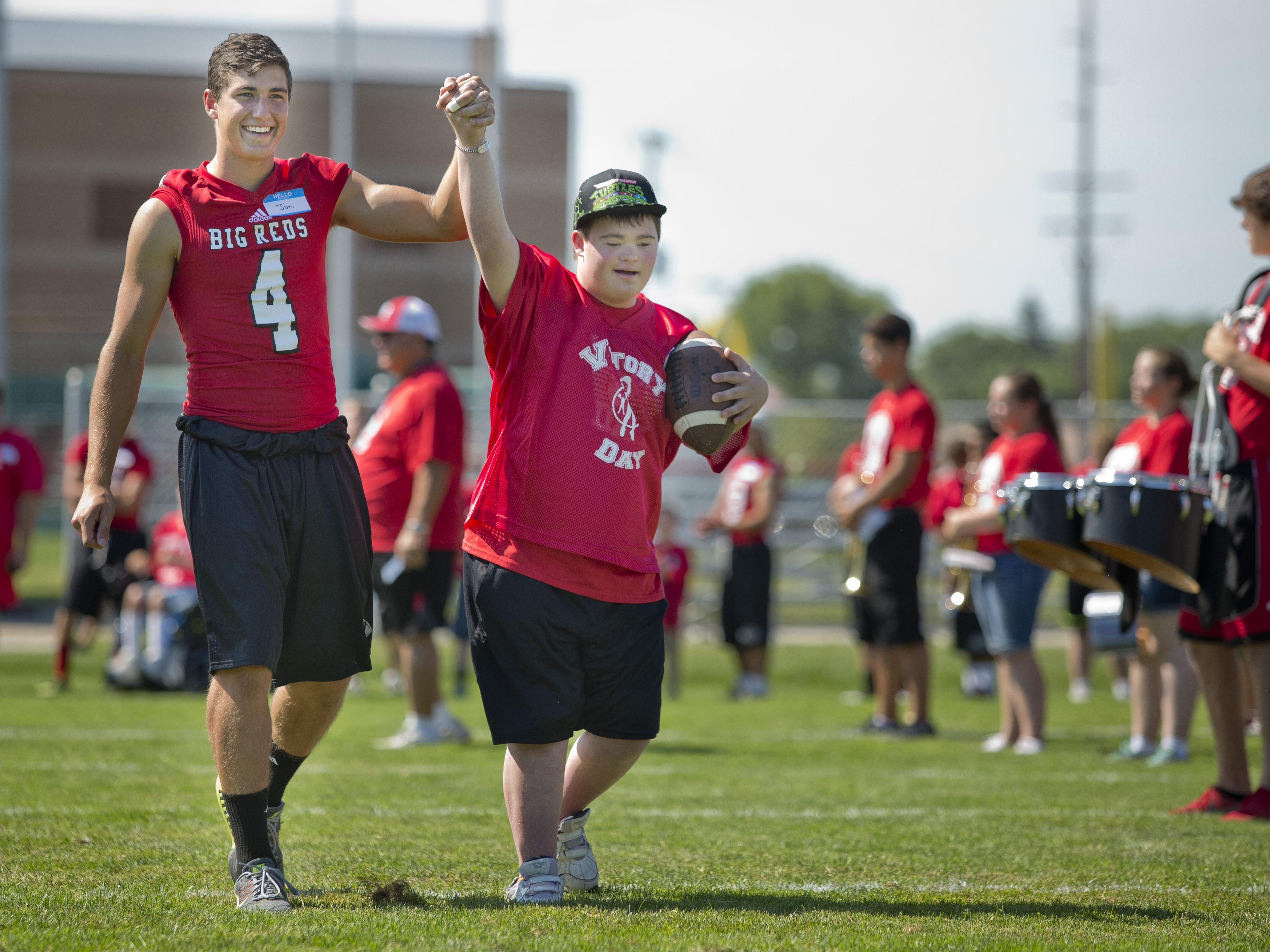Jon Miller and Cole DiNardo hold up their hands as they are introduced during Victory Day Saturday, August 15, 2015 in Memorial Stadium at Port Huron High School. The event paired special needs students with mentors from the football and cheerleading teams.