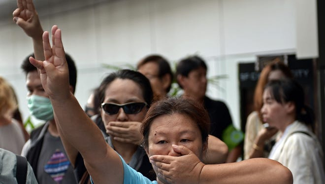 Anti-coup protesters flash a three-finger salute Sunday in downtown Bangkok.