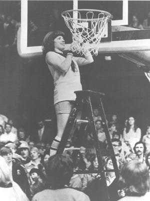 Judi Warren of Warsaw High School cuts down her portion of the net after winning the first girls state championship held at Hinkle Fieldhouse Feb. 28, 1976.