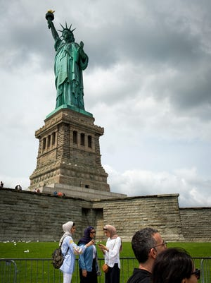 NEW YORK, NY - AUGUST 8: With the Statue of Liberty in the background, visitors pose for photos and walk around Liberty Island, August 8, 2017 in New York City. (Photo by Drew Angerer/Getty Images)