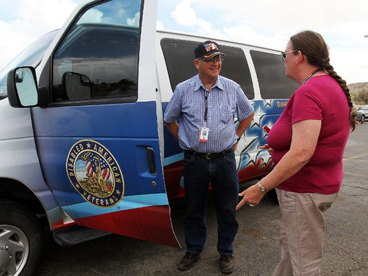 Doug Troxel, a volunteer driver for the Farmington unit of Disabled American Veterans van, goes over reports with Brenda Hunt, the van coordinator, after a trip to take a veteran to a doctor's appointment in Albuquerque.