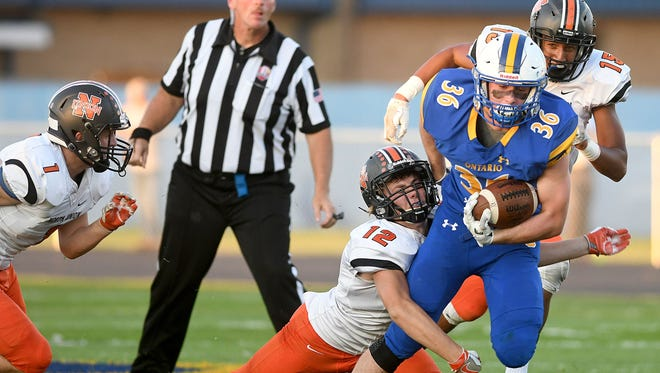 Ontario's Nick Arnold tries to avoid the tackle of Wes Cope of North Union on Friday night at Ontario High School.