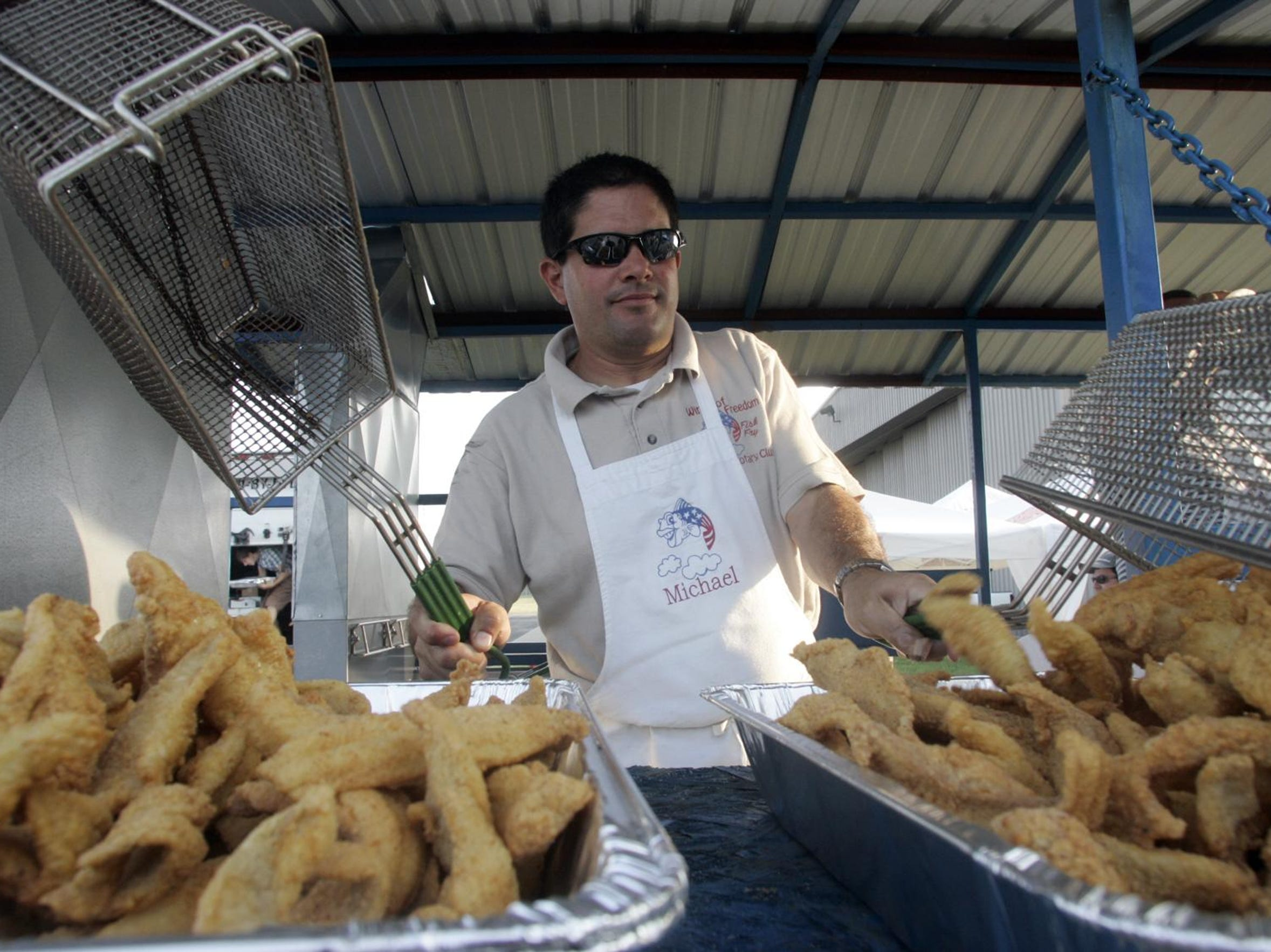 Michael Intorcia fills a tray with fried fish at a