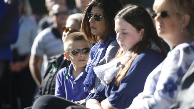Erika Slizewski-Smith, her son Hunter, 11, and daughter Gabbie, 14, sit in on a ceremony for fallen officers, including her husband Deputy Chris Smith, who lost his life in the line of duty on Nov. 22, 2014, at the Leon County Sheriff's Office Friday.