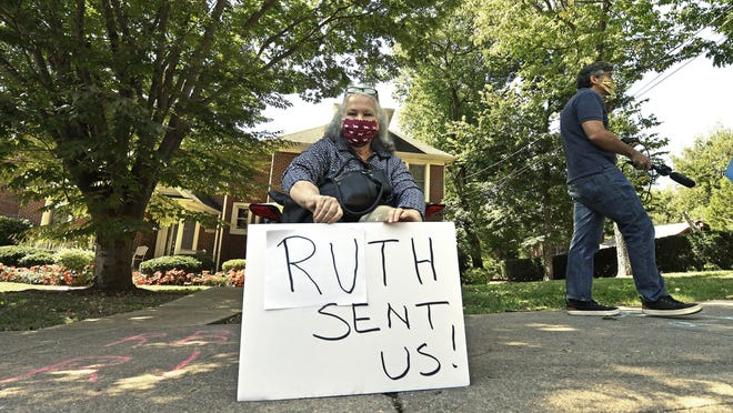 A protesters sits outside the house of Senate Majority Leader Mitch McConnell, R-Ky., in Louisville, Ky., Saturday, Sept. 19, 2020. McConnell vowed on Friday night, hours after the death of Supreme Court Justice Ruth Bader Ginsburg to call a vote for whomever President Donald Trump nominated as her replacement.