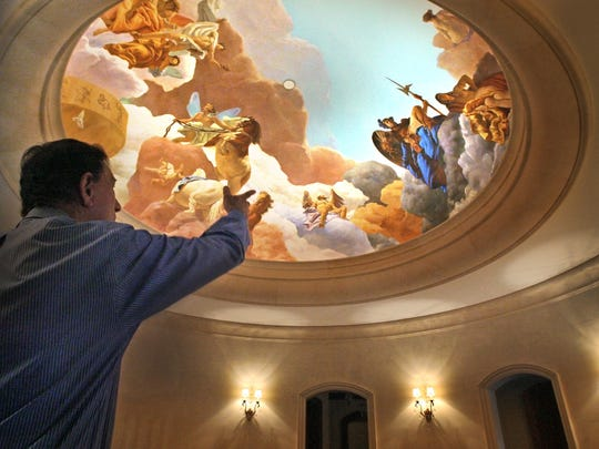 Forrest Lucas is shown pointing to the Stephen Hilbert-in-toga mural at Hilbert's former home, Le Chateau Renaissance, in Carmel. Lucas bought the home for $3 million.