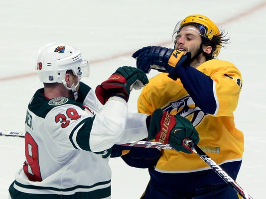 Minnesota Wild defenseman Nate Prosser (39) shoves Nashville Predators right wing Ryan Hartman, right, during the second period of an NHL hockey game Tuesday, March 27, 2018, in Nashville, Tenn. (AP Photo/Mark Zaleski)