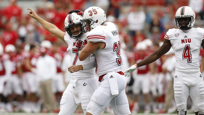 Northern Illinois Huskies quarterback Daniel Santacaterina (7) celebrates with tight end Shane Wimann (35) after defeating the Nebraska Cornhuskers in the second half at Memorial Stadium. Northern Illinois won 21-17.
