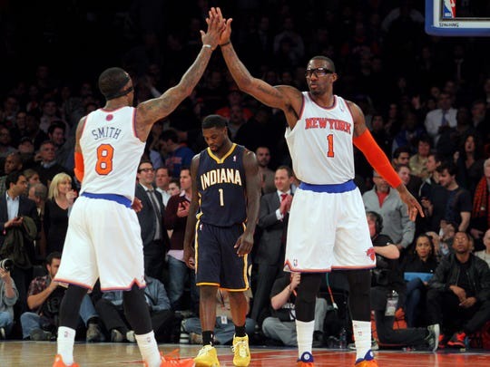New York Knicks shooting guard J.R. Smith (8) and New York Knicks power forward Amar'e Stoudemire (1) high five in front of Indiana Pacers shooting guard Lance Stephenson (1) during the fourth quarter of a game at Madison Square Garden. The Knicks defeated the Pacers 92-86.