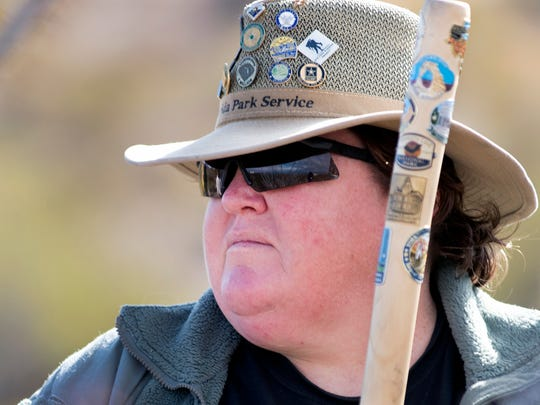 "Virginia ""Frenchie"" Bisiaux, of El Paso, Texas, rests on her walking stick during an informational stop along the Mogollon Trail at Leasburg Dam State Park as part of the First Day Hikes program sponsored by America's State Parks."