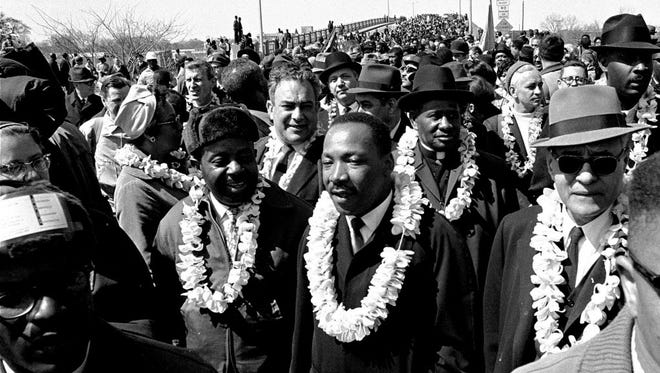 This March 21, 1965 file photo shows Martin Luther King, Jr. and his civil rights marchers crossing the Edmund Pettus Bridge in Selma, Ala., heading for the capitol in Montgomery. Tourists can retrace history by walking across the bridge to a park and the National Voting Rights Museum on the opposite side. (AP Photo, File)