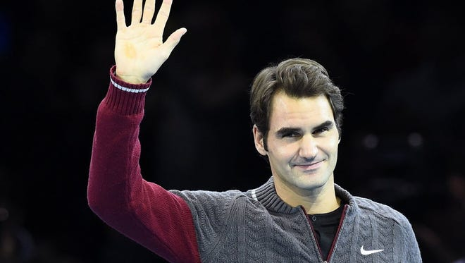 Roger Federer of Switzerland waves as he arrives to announce that he is injured and unfit to play Novak Djokovic of Serbia in the men's singles final tennis match at the ATP World Tour Finals at the O2 in London.