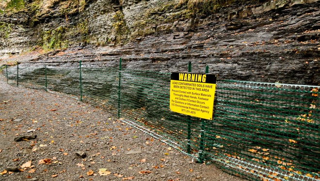 A sign warning of lead contamination is attached to a temporary fence warning of potential contamination on the floor of the Ithaca Falls Gorge.