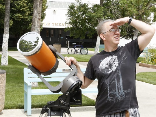 San Juan College Planetarium director David Mayeux examines the sun while displaying one of the telescopes that will be used for a solar eclipse watch party he'll be leading on Aug. 21.