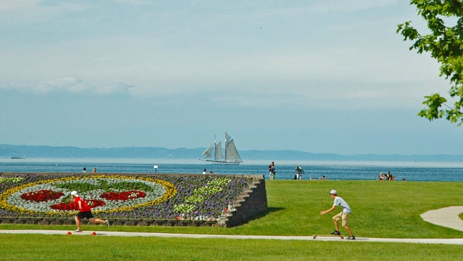 In this undated file photo, people enjoy a summer day in the Open Space park by Grand Traverse Bay in Traverse City, Mich.