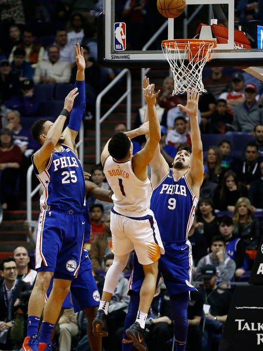 Phoenix Suns guard Devin Booker (1) has his shot altered by Philadelphia 76ers forward Dario Saric (9) and guard Ben Simmons (25) during the first half of an NBA basketball game, Sunday, Dec. 31, 2017, in Phoenix. (AP Photo/Ross D. Franklin)