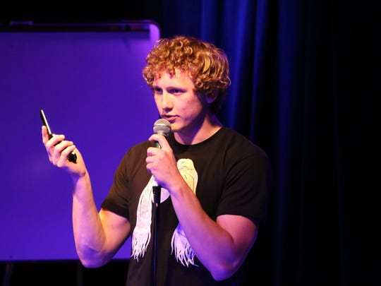 Andrew Van Hulzen -- holding his eight-year-old flip phone to help illustrate a joke -- performs Monday, April 20, 2015, in the Maintenance Shop on the Iowa State University campus in Ames. Finals for the third semester of ISU's Comedy College honors were held in the small nightclub in the basement of the Memorial Union.
