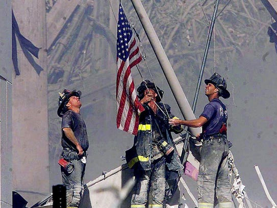 Firefighters raise a flag at the World Trade Center