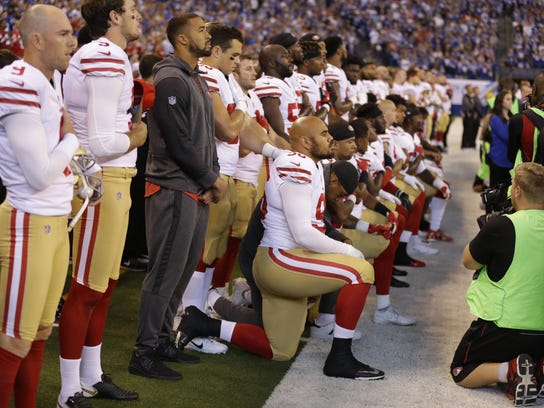 Members of the San Francisco 49ers kneel during the playing of the national anthem before an NFL football game against the Indianapolis Colts, Sunday, Oct. 8, 2017.