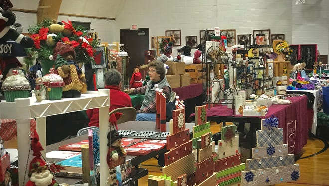 Vendors at Holy Cross Parish Center display crafts, food and other holiday products for sale during Mishicot's annual Christmas In The Village event.