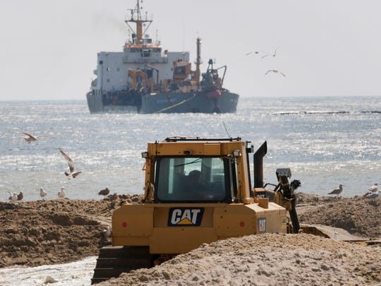 A boat sits just off shore as it pumps its load of sand onto the beach in Belmar in April.